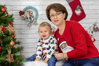Sedinta foto langa bradul de Craciun ornat cu globulete rosii si stelute aurii, cu mama imbracata in rosu impreuna cu baietelul ei de 1 an.