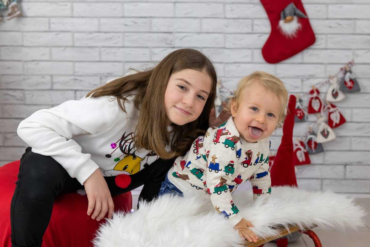 Sedinta foto langa bradul de Craciun ornat cu globulete rosii si stelute aurii, cu fetita alaturi de fratiorul ei de 1 an.
